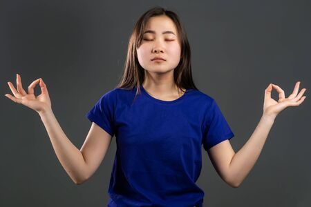 Calm korean girl relaxing, meditating. Woman calms down, breathes deeply with mudra om on grey studio background