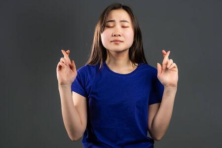 Cute asian young girl praying over grey background. Korean woman in glasses begging someone.