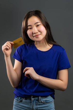 Successful pretty asian girl look to camera and showing unlimited gold credit card on grey studio background.