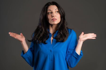 Mature unsure woman shrugs her arms, makes gesture of I dont know, care, cant help anything . Adult lady on grey background