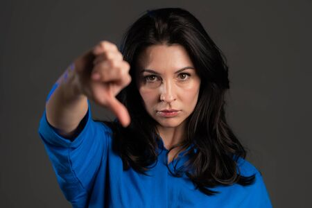 Adult woman standing on grey studio background showing thumb down gesture and expressing discontent at camera. Portrait of spanish woman with sign of dislike.