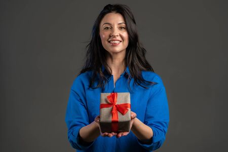Excited adult woman received gift box with bow. She is happy and flattered by attention. Mature lady dancing with present on grey background. Studio portrait