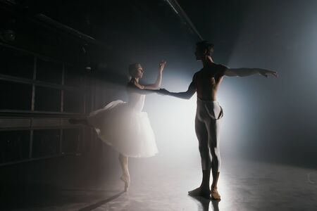 Professional ballet couple dancing in spotlights smoke on big stage. Beautiful young woman and man on floodlights background. Emotional duet performing choreographic art.