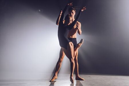 Beautiful young acrobats or gymnasts on floodlights background. Professional ballet couple dancing in spotlights smoke on big stage. Emotional duet performing choreographic art Фото со стока