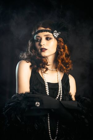 Portrait of old-fashioned red haired woman dressed in style of Great Gatsby era flirting and posing on burgundy velours background. Vintage, flapper party, retro fashion concept