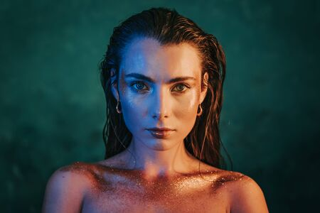 Portrait of young beautiful model girl with original golden make-up and sparkles on blue background.Concept of haute couture, art visage, femininity.