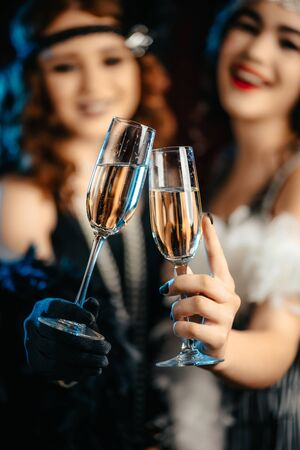 Beautiful flappers women dressed in style of Roaring twenties drinking champagne. Vintage, retro party, fashion, girls friends concept 版權商用圖片