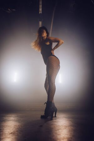 Beautiful woman with long hair in sexy clothes is dancing in dark room. Modern dance, lifestyle, talented girl.