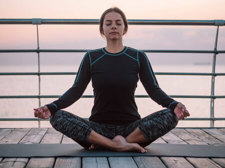 Concentrated girl in black practicing in yoga meditation on wooden seafront. Woman in lotus pose. Stretching, practice, healthy lifestyle concept. Copy space 版權商用圖片