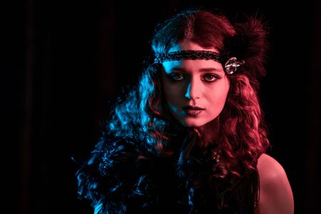 Old-fashioned woman dressed in style of Great Gatsby posing on dark background with neon light. Roaring twenties, retro, party, fashion concept.