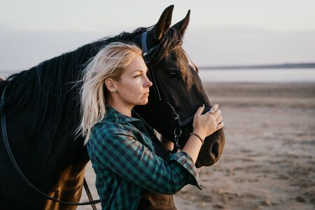 Portrait of adult woman with beautiful horse in nature. Sunlight, silhouette.Concept of love for lesser brothers, caring and animal training 版權商用圖片