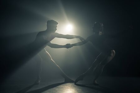 Professional ballet couple dancing in spotlights smoke on big stage. Beautiful young woman and man on floodlights background. Emotional duet performing choreographic art. 版權商用圖片