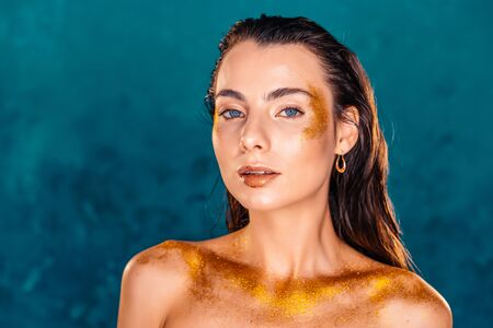 Perfect naked girl covered with gold paint and shimmering sparkles on green wall in studio. Glowing woman, high fashion concept.