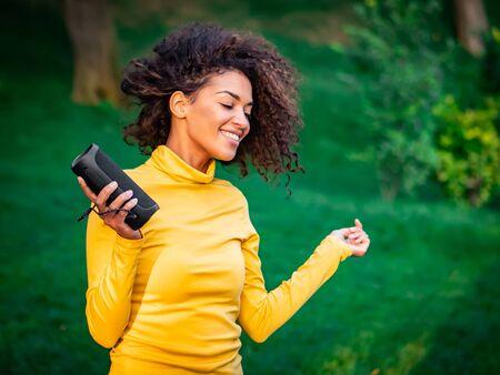 Modern trendy african american girl listening to music by wireless portable speaker.Young beautiful woman enjoying, dancing in park. 版權商用圖片