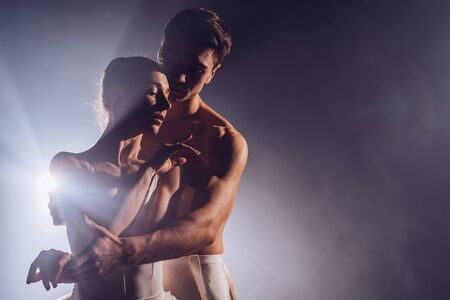 Pair touching each other with hands and passion. Love concept. Professional, sensual ballet dancers performed by sexual couple in white wear.