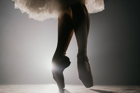Close up of ballet dancer as she practices exercises on dark stage or studio. Womans feet in pointe shoes. Ballerina shows classic ballet pas. Slow motion. Flare shot.