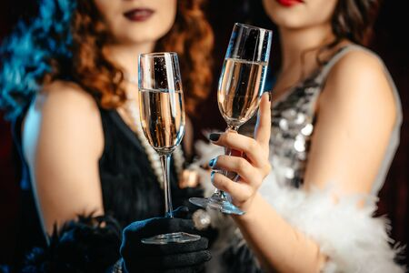 Close up glasses of champagne. Flappers women wearing in style of Roaring Gatsby twenties drinking alcohol. Vintage, retro party, fashion, girls friends concept