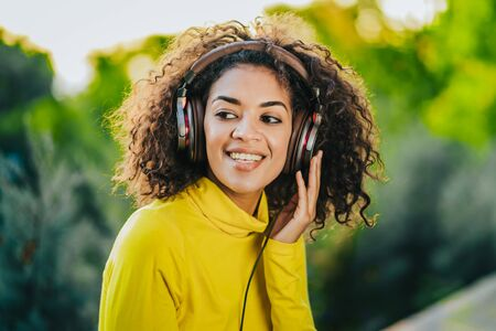 Close-up of african american woman listening to music with headphones outdoors. Young girl with curly hairstyle in yellow enjoys music in park.