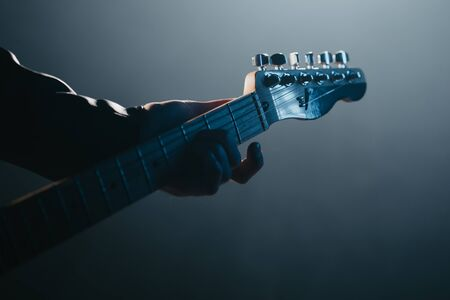Guitar neck. Close-up view of rock musician man playing electric guitar. Smoky spotlight during concert on stage.