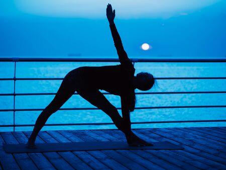 Yoga under full moon over night ocean or sea beach. Young womans meditation during practice. 版權商用圖片