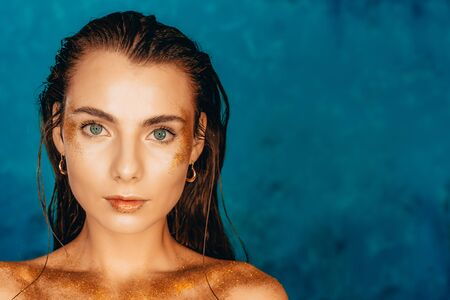 Portrait of glamour woman with golden body art on blue background. Fashionable girl with perfect healthy skin. Art, femininity concept. 版權商用圖片