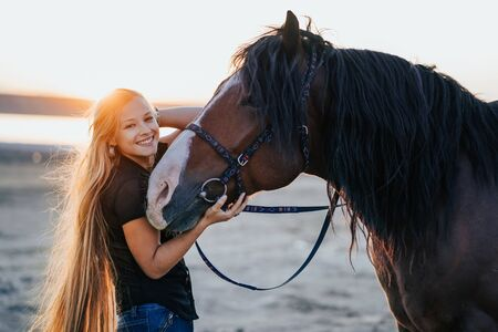 Blonde woman stroking and hugging horse. Beautiful lady with black stallion enjoying sunset nature. Love and friendship concept.