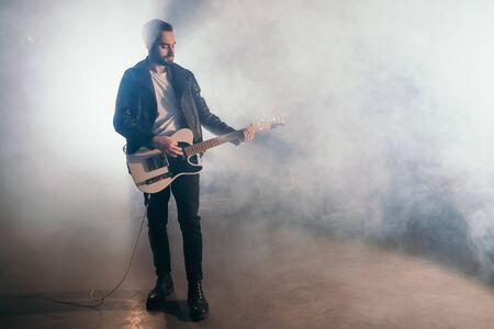 Rock guitarist man in leather jacket in smoky studio or stage masterfully playing electric guitar. View of musician in the spotlight. 版權商用圖片