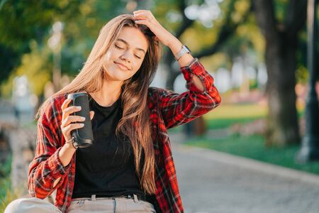 Modern trendy girl listening to music by wireless portable speaker.Young beautiful american woman enjoying,dancing in park.