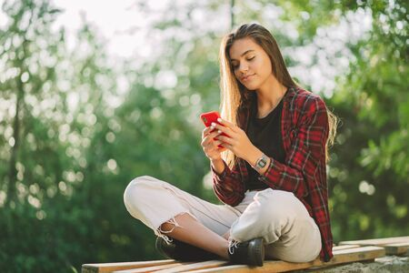 Young pretty woman sitting in green park and using mobile phone. Surfing internet, social networks, internet concept. 版權商用圖片