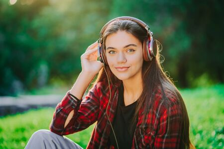 Portrait of attractive girl dancing with earphones in park. Woman smiling. moves to the rhythm.Friendly appearance of modern trendy hipster 版權商用圖片