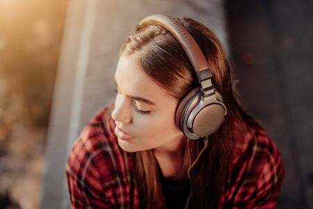 Young teenager listens to music through headphones in park.Girl in red plaid shirt smiles, dancing to rhythm.Concept of student life, freedom, modern youth 版權商用圖片