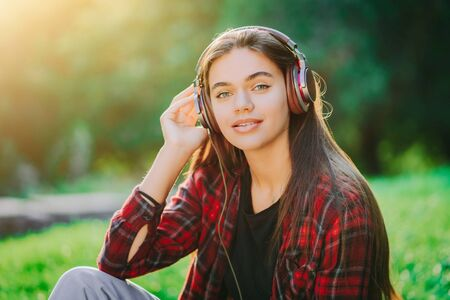 Cute girls face with headphones. Young woman enjoys music while sitting in green park. Concept of youth, freedom, technology