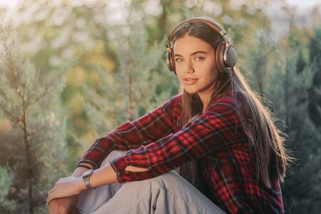 Young teenager listens to music through headphones in park.Girl in red plaid shirt smiles, dancing to rhythm.Concept of student life, freedom, modern youth Zdjęcie Seryjne