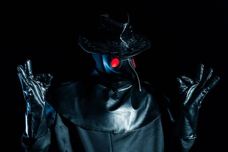 Man in plague doctor costume with crow-like mask meditating isolated on black background. Creepy mask, historical costume concept. Epidemic