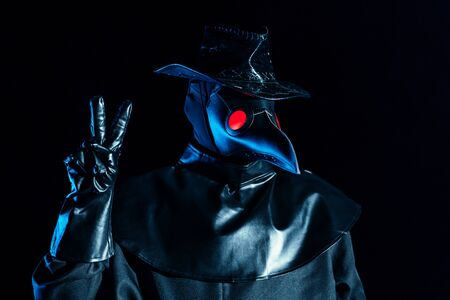 Man in plague doctor costume with crow-like mask showing peace gesture isolated on black background. Creepy mask, historical costume concept. Epidemic