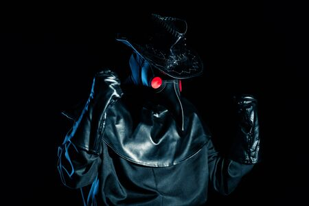 Man in plague doctor costume with crow-like mask showing yes winner gesture, rejoices isolated on black background. Creepy mask, historical costume concept. Epidemic