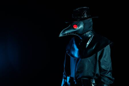 Portrait of plague doctor with crow-like mask isolated on black background. Creepy mask, halloween, historical terrible costume concept. Epidemic