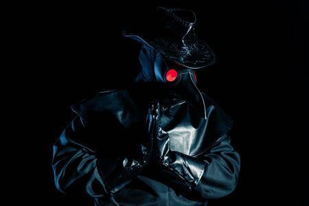Man in plague doctor costume with crow-like mask praying with hands isolated on black background. Creepy mask, historical costume concept. Epidemic