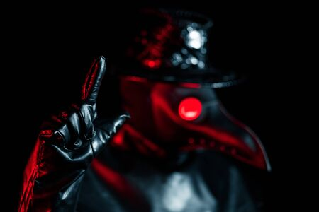 Plague doctor with crow-like mask disapproving with no finger sign, make negation gesture. Denying, Rejecting, Disagree isolated on black background. Creepy mask, historical costume concept. Epidemic Zdjęcie Seryjne