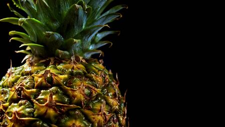 Juicy fresh big pineapple rotating on black background. Fruit isolated. Macro surface of tropical product. Zdjęcie Seryjne