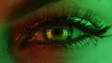 Extreme close up of human eye iris under neon light. Female with beautiful makeup, glitter shadows and false lashes. Womens green eye contracting. Nightlife, night club concept. Zdjęcie Seryjne