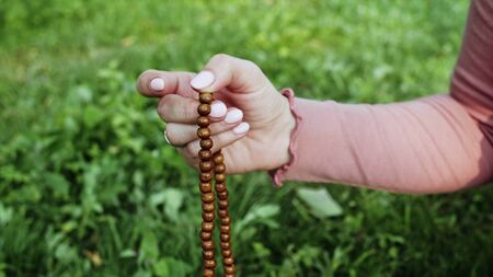 Woman lit hand close up counts rosary - malas strands of gemstones beads used for keeping count during mantra meditations. Girl sits on summer nature.