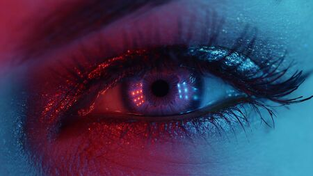 Extreme close up of human eye iris under neon light. Female with beautiful makeup, glitter shadows and false lashes. Womens green eye contracting. Nightlife, night club concept. Banco de Imagens