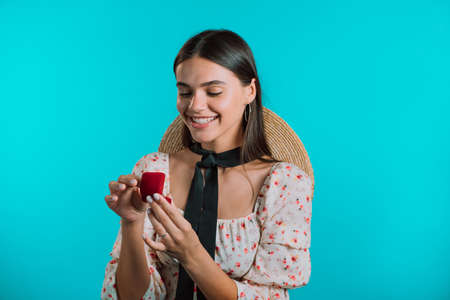 Attractive young woman holding small jewelry box with proposal diamond ring on blue wall background. Lady smiling, she is happy to get present, proposition for marriage