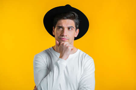 Thinking hipster man looking up and around on yellow background. Pensive face expressions. Handsome male model.