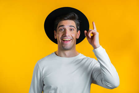 Smiling happy guy showing eureka gesture. Portrait of young man having idea moment pointing finger up on yellow studio background.