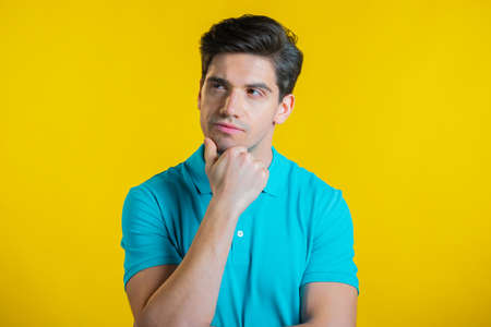 Thinking man looking up and around on yellow background. Pensive face expressions. Handsome male model.