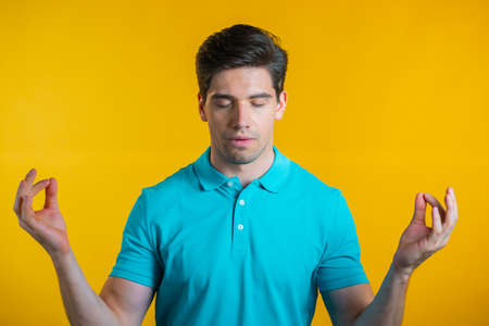 Calm man in blue relaxing, meditating. He calms down, breathes deeply with mudra om on yellow studio background. Yoga concept. Banco de Imagens