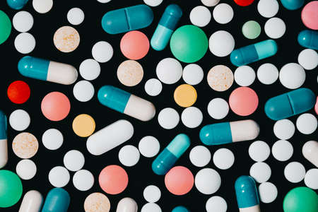 Pharmacy theme. Multicolored Isolated Pills and Capsules on Black Surface. Vitamins, drugs concept. COVID-19, Coronavirus, epidemic 版權商用圖片