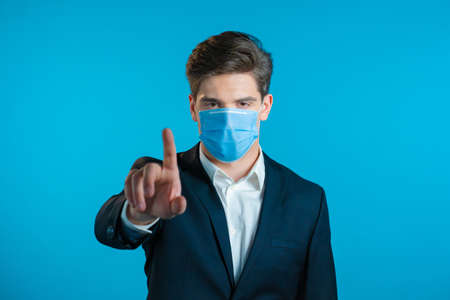 Portrait of serious businessman in professional suit and medical mask showing rejecting gesture by stop finger sign. Man isolated on blue background. Zdjęcie Seryjne